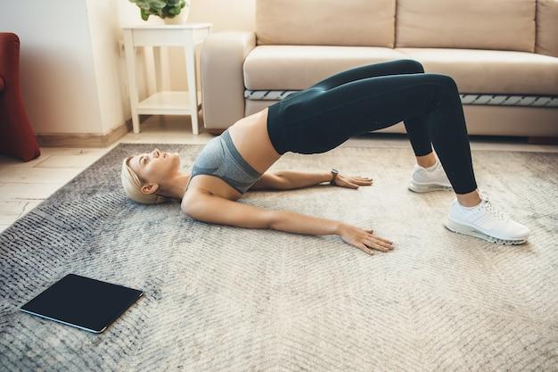 Blonde vrouw in activewear is aan het opwarmen op de vloer met een tablet in de buurt van haar