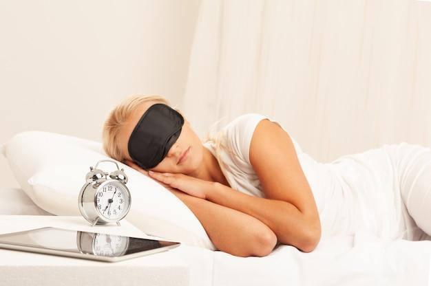Blonde vrouw in bed die 's ochtends geïrriteerd naar haar wekker kijkt