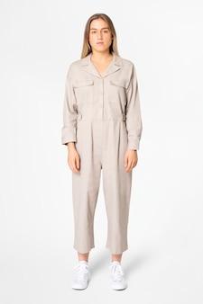 Blonde vrouw in beige jumpsuit met streetwear-kleding in designruimte