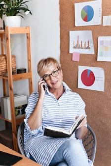 Blonde vrouw in blauw shirt en bril praten telefoon en houdt notebook