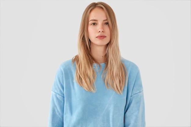 Blonde vrouw in blauw shirt poseren