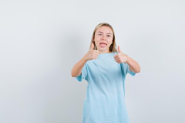Blonde vrouw in blauw t-shirt met dubbele duimen omhoog, tong uitsteekt