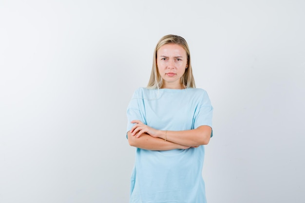 Blonde vrouw in blauw t-shirt staande armen gekruist en serieus kijken