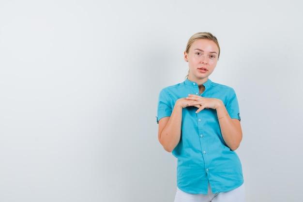 Blonde vrouw in blauwe blouse die handen op de borst houdt en er delicaat geïsoleerd uitziet Gratis Foto