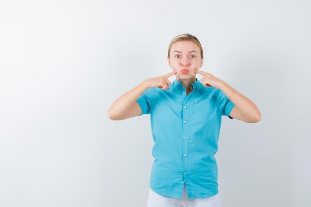 Blonde vrouw in blauwe blouse die vingers op gezwollen wangen houdt en er schattig geïsoleerd uitziet