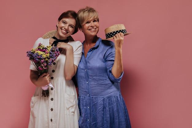Blonde vrouw in blauwe jurk stro hoed houden en lachend met kortharige meisje in lichte kleren met kleurrijke wilde bloemen op roze achtergrond.