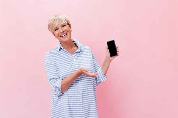 Blonde vrouw in blauwe outfit toont smartphone op roze achtergrond