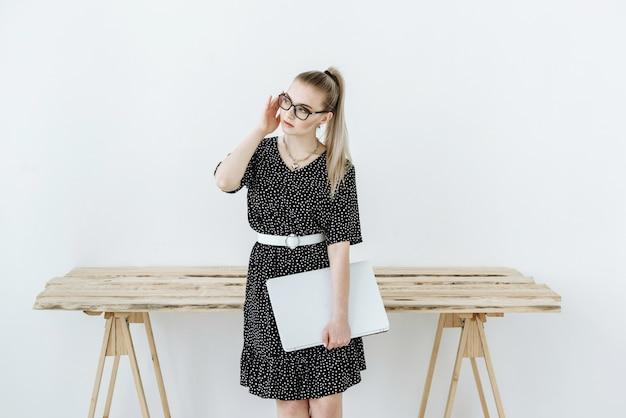 Blonde vrouw in bril en jurk met laptop