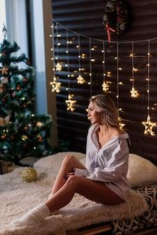 Blonde vrouw in de buurt van dennenboom voor viering van nieuwjaar en kerstmis. hoge kwaliteit foto