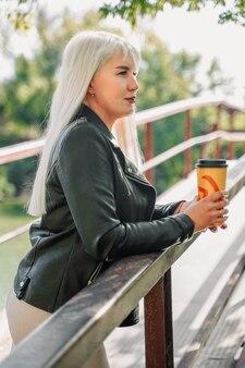 Blonde vrouw in de stadsstraat die een warme drank drinkt en naar één kant kijkt mooi meisje met een kopje ...