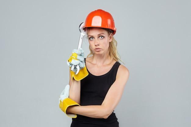 Blonde vrouw. in een beschermende helm en handschoenen, met een grote sleutel.
