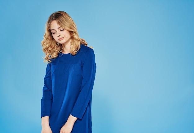 Blonde vrouw in een blauwe jurk op blauwe muur