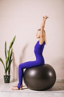 Blonde vrouw in een gesloten sport jumpsuit van blauwe kleur beoefenen van yoga zit op een fitball met haar armen omhoog in een kamer bij de muur
