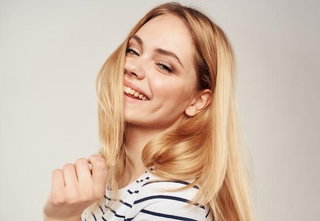 Blonde vrouw in een gestreepte t-shirt op een beige achtergrond bijgesneden weergave close-up
