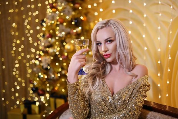 Blonde vrouw in een gouden kerst set