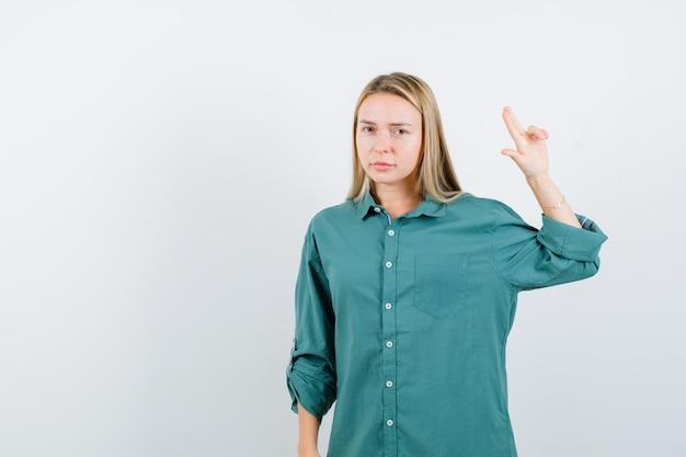 Blonde vrouw in een groen shirt die een vingerpistool maakt en er zelfverzekerd uitziet?