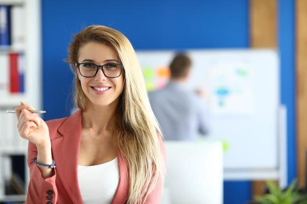 Blonde vrouw in een jasje met bril staat op kantoor en glimlacht. overleg met klanten in het bankconcept