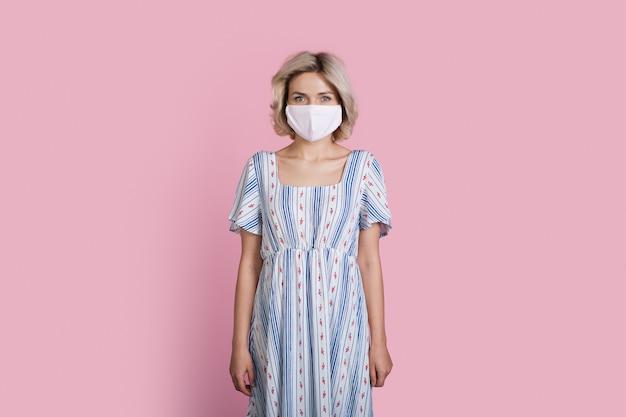Blonde vrouw in een lange zomerjurk draagt een medisch masker op een roze muur