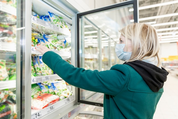Blonde vrouw in een medisch masker is winkelen bij een supermarkt in de diepvriesafdeling. quarantaine tijdens de pandemie van het coronavirus.
