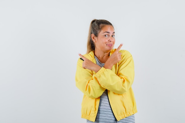 Blonde vrouw in geel bomberjack en gestreept overhemd die verschillende richtingen met wijsvinger richten en er mooi uitzien