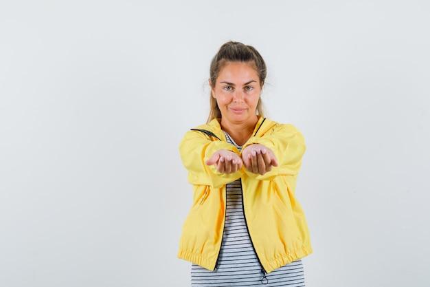 Blonde vrouw in geel bomberjack en gestreept overhemd handen uitrekken als iets ontvangen en er mooi uitzien