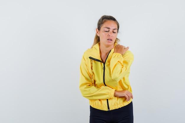 Blonde vrouw in geel bomberjack en zwarte broek balde vuist terwijl ze naar de onderkant kijkt en gefocust kijkt