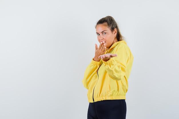 Blonde vrouw in geel bomberjack en zwarte broek die kusjes verzendt terwijl ze haar hand naar voren strekt en er gelukkig uitziet