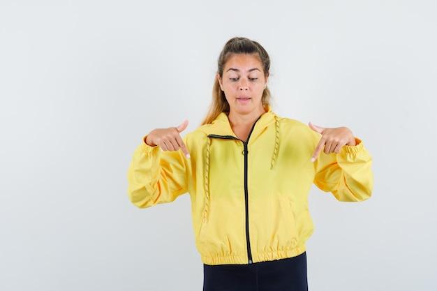 Blonde vrouw in geel bomberjack en zwarte broek die met wijsvingers naar beneden wijst en er serieus uitziet