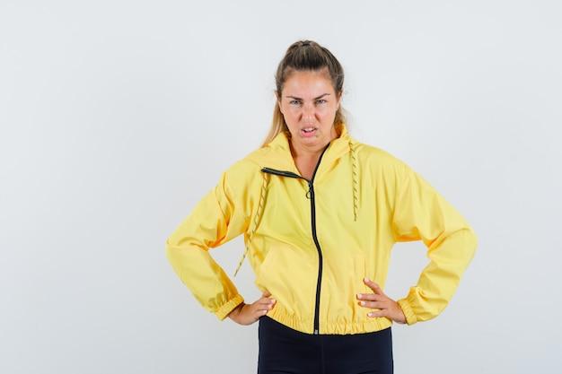 Blonde vrouw in geel bomberjack en zwarte broek hand in hand op taille, grimassen en op zoek woedend