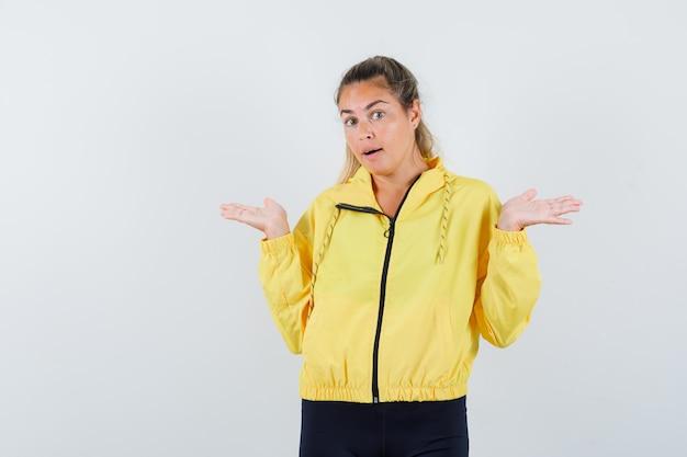 Blonde vrouw in geel bomberjack en zwarte broek strekt zich uit over de handen op vragende wijze en kijkt verbaasd