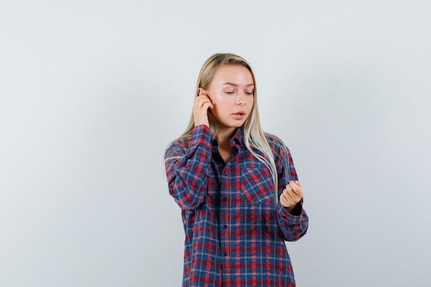 Blonde vrouw in geruit overhemd die doet alsof ze aan de telefoon praat terwijl ze naar de hand kijkt terwijl ze iets vasthoudt en gefocust kijkt, vooraanzicht.