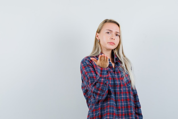 Blonde vrouw in geruit overhemd die één hand naar camera uitrekt als proberend om iets te ontvangen en nieuwsgierig, vooraanzicht kijkt.