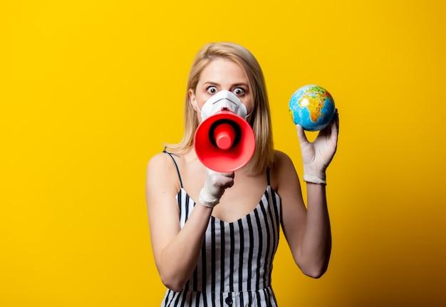 Blonde vrouw in gezichtsmasker en handschoenen houdt earth globe en megafoon