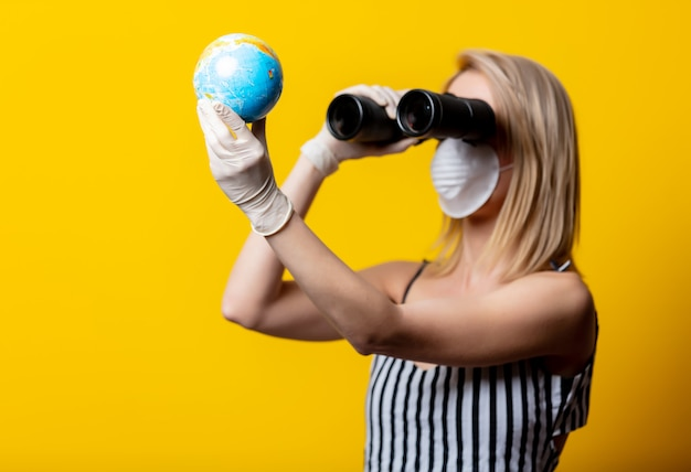 Blonde vrouw in gezichtsmasker en handschoenen houdt earth globe en verrekijker