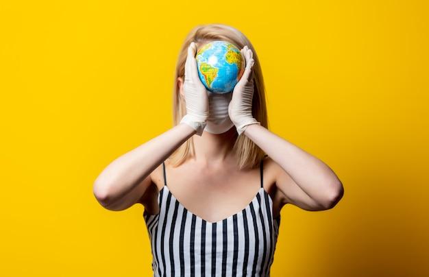 Blonde vrouw in gezichtsmasker en handschoenen houdt earth globe