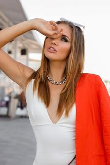 Blonde vrouw in grote zonnebril met volle lippen buiten poseren. rood jasje, stijlvolle zilveren accessoires. perfect figuur.