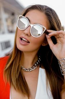 Blonde vrouw in grote zonnebril met volle lippen buiten poseren. rood jasje, stijlvolle zilveren accessoires.