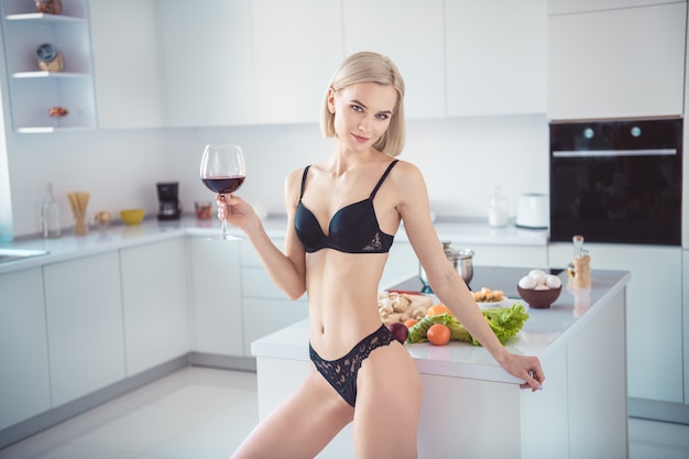 Blonde vrouw in haar lingerie poseren in de keuken