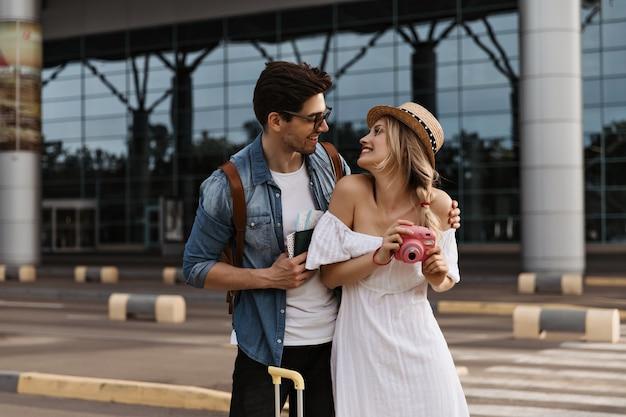 Blonde vrouw in hoed en witte jurk glimlacht, kijkt naar vriendje en houdt roze camera vast