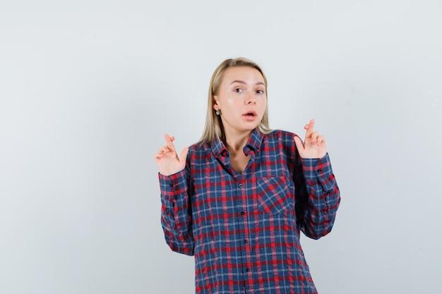 Blonde vrouw in ingecheckte overhemd vingers gekruist en op zoek verrast, vooraanzicht.