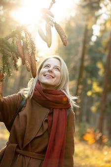 Blonde vrouw in jas en rode sjaal houdt dennen tak met kegels in een bos