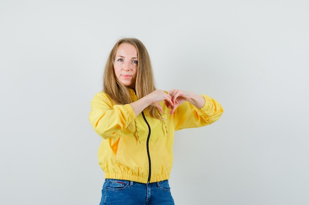 Blonde vrouw in jasje, spijkerbroek hart gebaar tonen en vrolijk kijken,