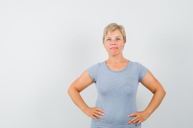 Blonde vrouw in lichtblauw t-shirt met haar handen op de taille en op zoek naar zelfverzekerd, vooraanzicht.