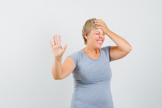 Blonde vrouw in lichtblauw t-shirt met weigering gebaar en houdt haar hand op het hoofd en kijkt geïrriteerd, vooraanzicht.