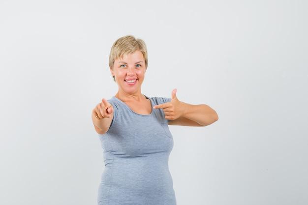 Blonde vrouw in lichtblauw t-shirt voor haar oren met haar handen en glimlachend en op zoek optimistisch, vooraanzicht.