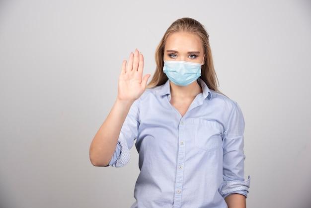 Blonde vrouw in medisch masker die nummer vijf met hand toont.