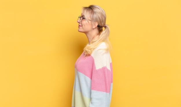 Blonde vrouw in profielweergave die ruimte vooruit wil kopiëren, denken, fantaseren of dagdromen