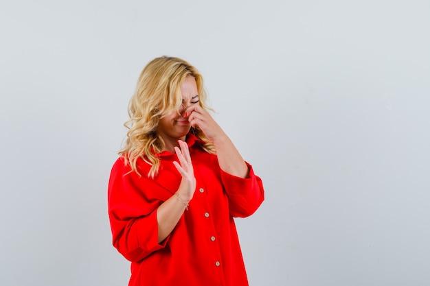 Blonde vrouw in rode blouse neus knijpen vanwege geur en op zoek geërgerd,