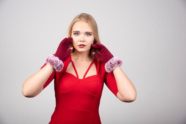 Blonde vrouw in rode cocktailjurk camera kijken.