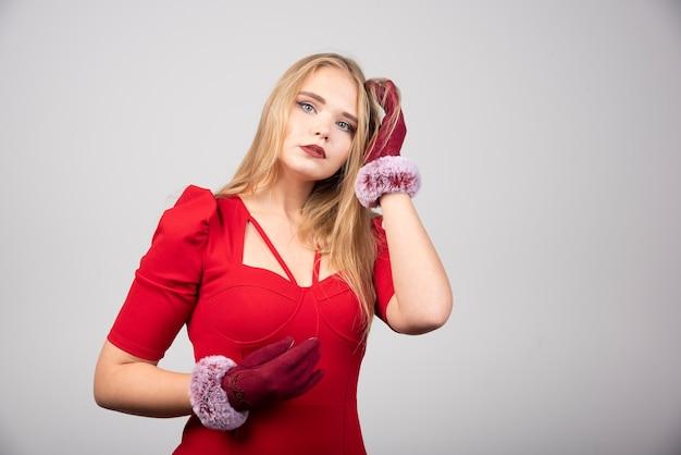 Blonde vrouw in rode cocktailjurk staande op een grijze achtergrond.
